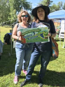 Two Beyond Indian Point supporters hold up a BIP sign at an outdoor event