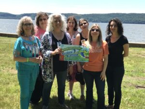 seven Beyond Indian Point supporters hold up a BIP sign with the Hudson river in the background