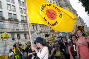 large crowd of people marching and chanting with the person in front holding up a bright yellow anti-nuclear power flag